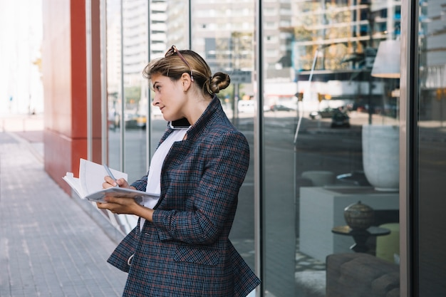 Side young businesswoman writing in the notebook with pen Free Photo
