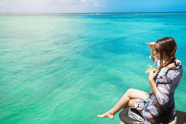 Sideview of cheerful woman sitting on pier admiring fantastic ocean Premium Photo