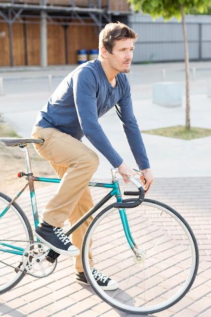 Вид сбоку человек, езда на велосипеде на открытом воздухе Бесплатные Фотографии