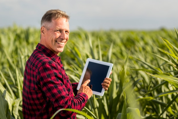 Sideview man with a tablet in a maize field mock-up Free Photo