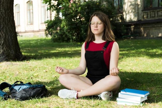 Sideview of meditating highschool girl Free Photo