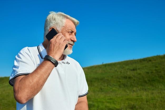 晴れた日の間に携帯電話で話しているスポーツマンの横顔。 Premium写真