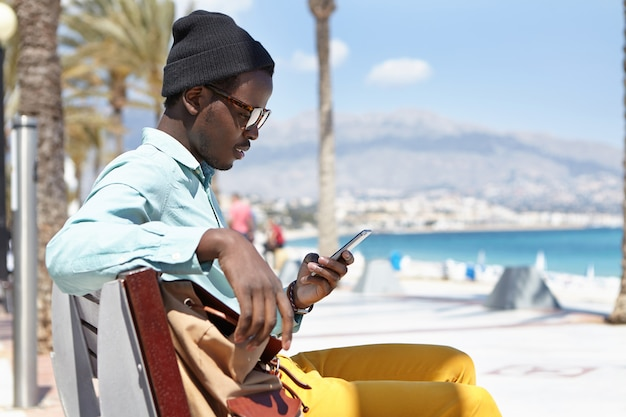 Sideview outdoor portrait of cheerful stylish young afro american man sitting on bench along promenade at seaside, using free city wi-fi while chatting with friends via social networks on cell phone Free Photo