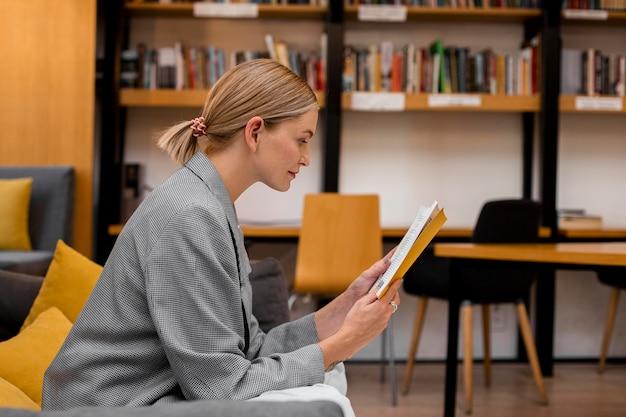 図書館で読書をしているサイドビューの学生 無料写真
