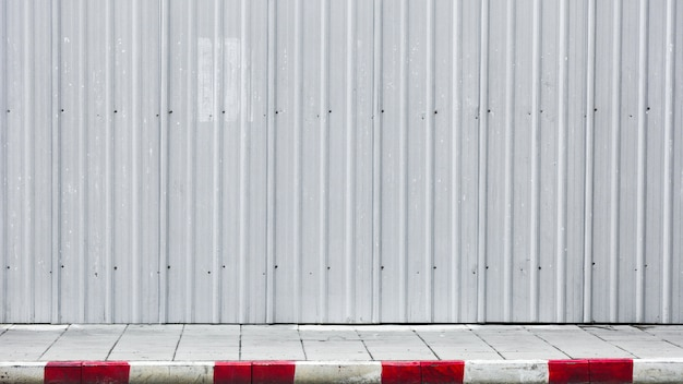 Sidewalk and curb red-white with metal corrugated wall Premium Photo