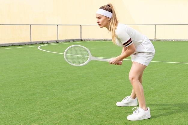 Sideway tennis woman with racket Free Photo