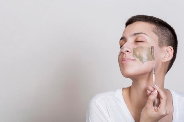 Sideway woman applying on cheek mud treatment Free Photo