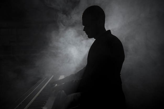Художник сбоку играет на фортепиано с эффектами дыма и теней Бесплатные Фотографии