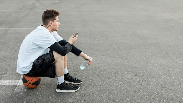 Sideways basketball player checking his phone Free Photo