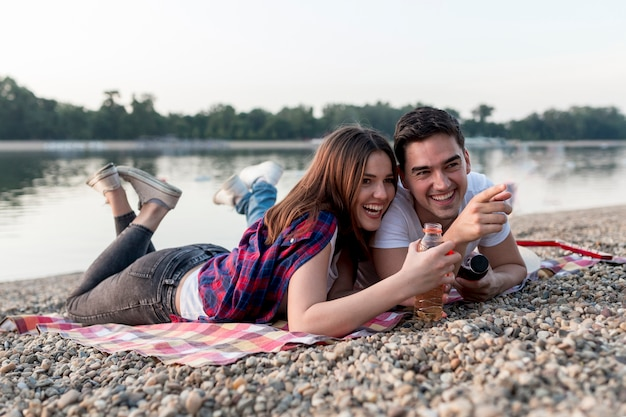Sideways couple on a date lying on picnic blanket Free Photo