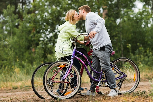 Sideways couple kissing on bicycles Free Photo
