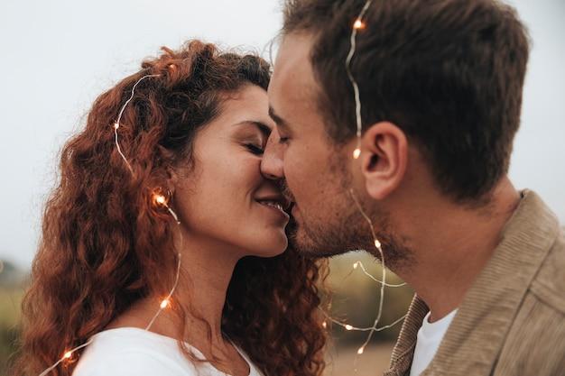 Sideways couple kissing outdoors Free Photo