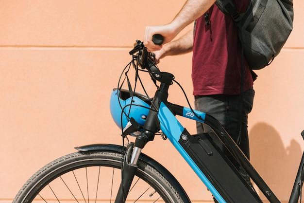 Sideways cyclist standing next to e-bike Free Photo