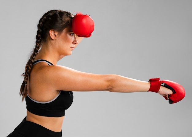 Sideways girl punching with box gloves Free Photo