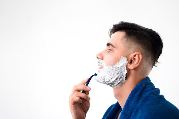 Sideways handsome man shaving his beard close-up Free Photo