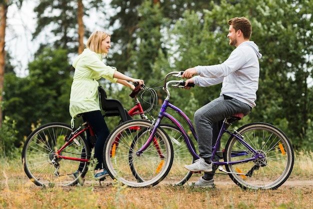 Sideways happy couple on bicycles Free Photo