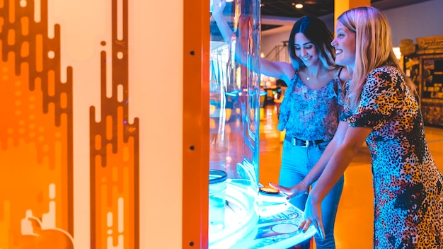 Sideways happy women playing arcade game Free Photo