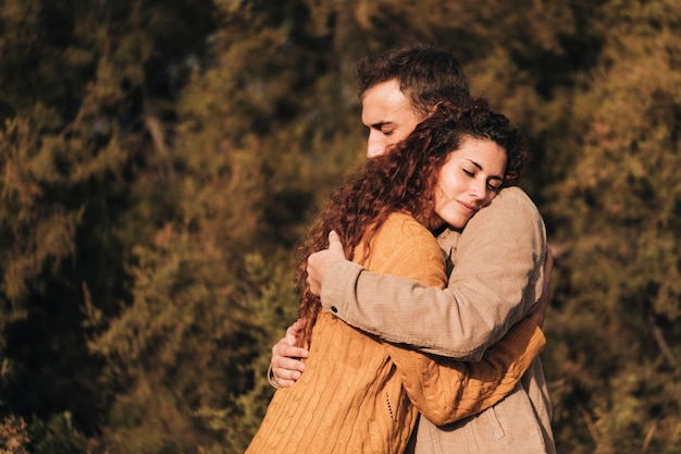 Sideways hugging couple outdoors Free Photo
