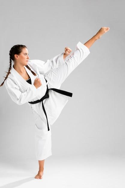 Sideways karate woman in traditional white kimono on white background Free Photo