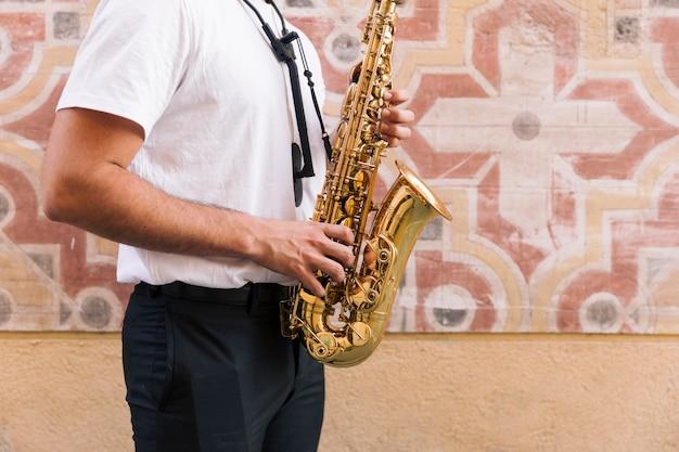 Sideways man medium shot playing the saxophone with geometric background Free Photo