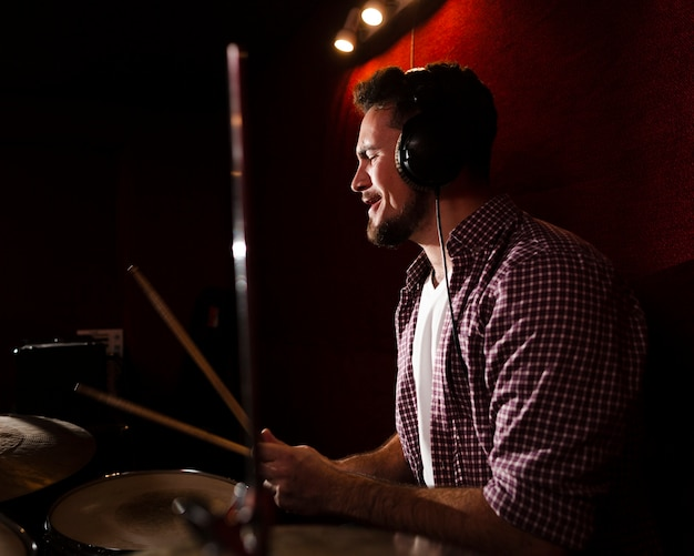 Sideways man playing drums and wearing headphones Free Photo