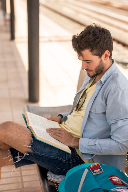Sideways of a man reading a book on train station Free Photo