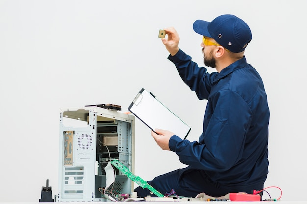 Sideways man repairing a computer Free Photo