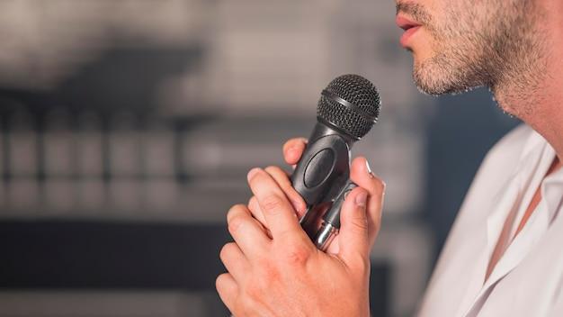 Sideways man singing at microphone Free Photo