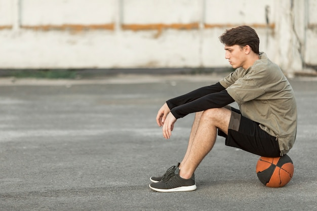 Sideways man sitting on a basketball Free Photo