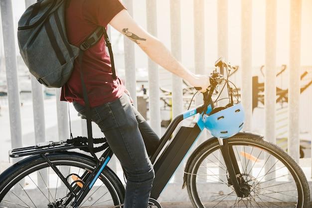 Sideways medium shot cyclist riding an e-bike Free Photo