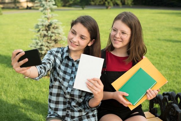 Sideways medium shot of teenage girls taking a selfie Free Photo