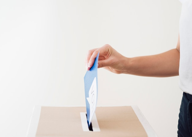 Sideways person putting ballot in box Free Photo