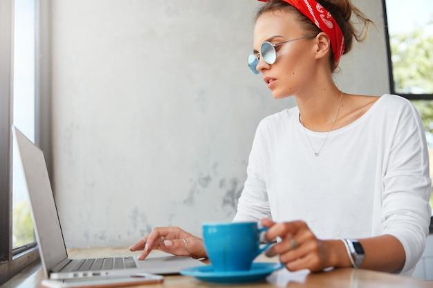 Боковой портрет сосредоточенной молодой красивой девушки-графического дизайнера в модных тонах, работает за современным ноутбуком и пьет кофе, проводит обеденный перерыв в кафетерии, готовит проектную работу. Бесплатные Фотографии