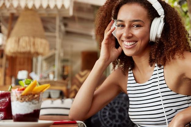 黒い髪の黒い肌の女性の横向きの肖像画は、音楽やオーディオブックを聴くために高品質のヘッドフォンと携帯電話を使用し、カフェで余暇を過ごし、高速インターネットを楽しんでいます 無料写真