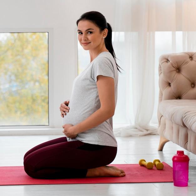 Боковая беременная женщина занимается йогой Бесплатные Фотографии