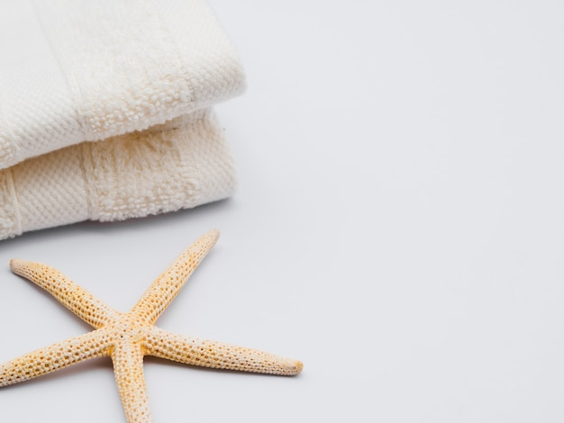 Sideways seastar and towels with copy space Free Photo