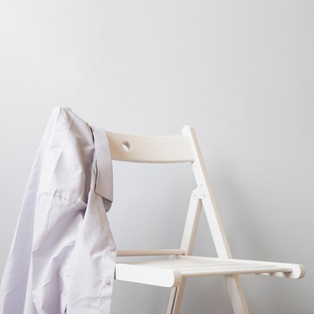 Sideways shirt on a white chair Free Photo