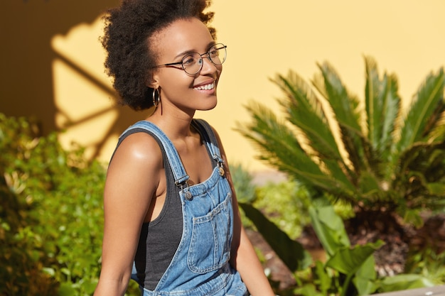 Il colpo laterale di una ragazza adolescente felice e giubilante ha un'acconciatura afro, indossa occhiali rotondi, tute di jeans, pose all'aperto su vista tropicale, muro giallo, spazio libero per i tuoi contenuti pubblicitari. Foto Gratuite