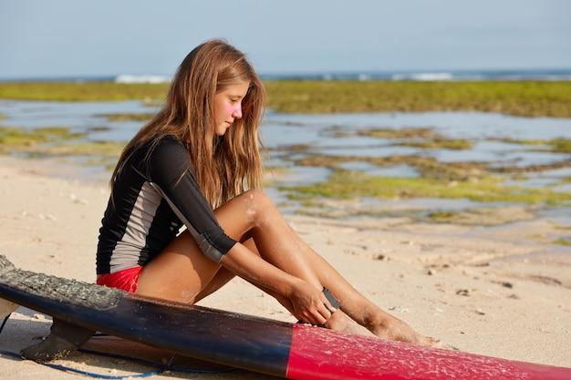 Снимок сбоку привлекательной стройной молодой девушки-серфингистки, которая пристегивает поводок на ноге, что позволяет не врезаться в каменистые берега. Бесплатные Фотографии