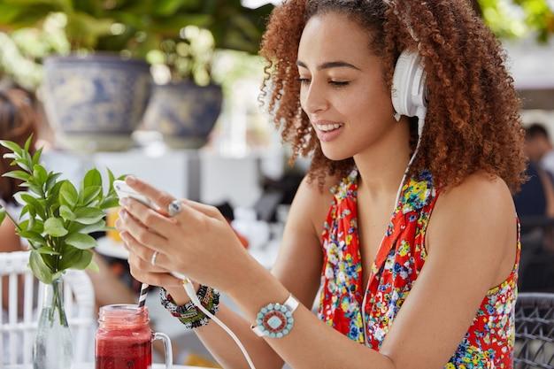 Боковой снимок красивой довольной молодой девушки веселится и смеется, слушая любимую композицию в наушниках, печатает сообщение парню Бесплатные Фотографии