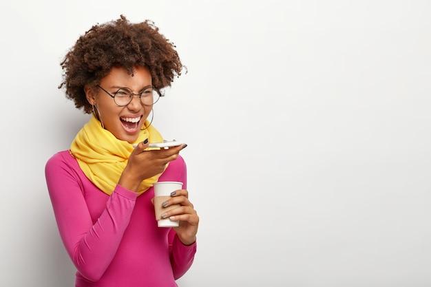 곱슬 머리를 가진 감정적 인 어두운 피부의 여성을 옆으로 촬영하고, 현대 휴대 전화에서 음성 인식 앱을 사용하고, 테이크 아웃 커피를 들고, 안경을 쓰고, 장밋빛 터틀넥을 착용하고, 흰 벽 위에 포즈를 취합니다. 무료 사진