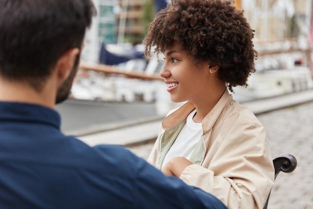 Боковой снимок счастливой девушки и парня, которые любят проводить время вместе, сидеть возле гавани, говорить о жизненных целях. Бесплатные Фотографии