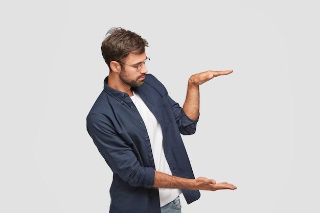 自信のある男性の横向きのショットは、何かのサイズまたは高さを示し、手のひらを空中に上げます 無料写真