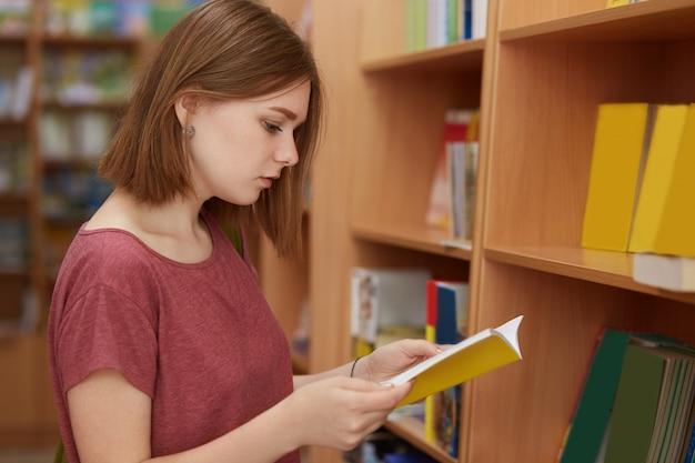 本に焦点を当てた深刻な大学生女子学生の横向きのショット、学校の図書館でポーズ、レポートの準備に必要な文献を選択、tシャツを着ています。 10代の若者、勉強と読書のコンセプト Premium写真
