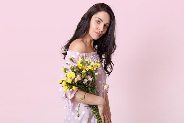 健康的な肌を持つ深刻な暗い髪の女性の横向きのショットは、ファッショナブルなドレスを着た花束を保持し、パステルピンクでポーズします。春が来る。国際婦人デー 無料写真
