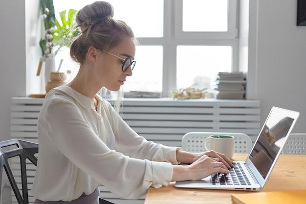Вид сбоку серьезной модной молодой европейской бизнес-леди в стильной белой блузке и круглых очках, которая работает на обычном электронном устройстве, проверяет электронную почту и пишет деловое письмо Бесплатные Фотографии