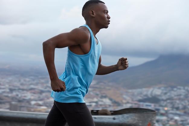 Снимок сбоку: спортивный темнокожий бегун в синем жилете, участвует в гонке по триатлону, ведет фитнес-образ жизни, модели на фоне размытых скал на открытом воздухе, сфотографированы в быстром движении. Бесплатные Фотографии