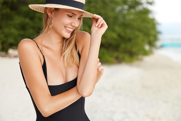 夏服の若い女性の横向きのショットは、リゾートの町で美しい景色と海を眺め、一人でビーチを散歩し、心地よい暖かい笑顔を持ち、見知らぬ人からの褒め言葉を受け取って喜んでいます。 無料写真