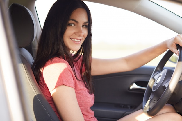 Sideways shot of pleasant looking brunette woman sits in her own automobile instructor Free Photo