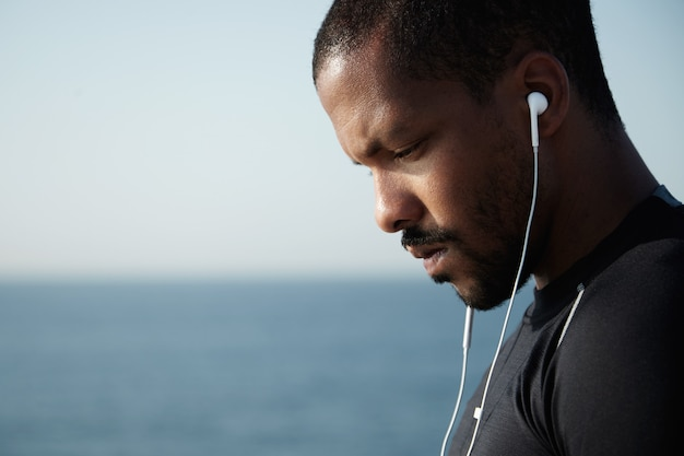 Sideways shot of sad african american man looking down and listening to melancholic music in headphones with serious, pensive face. Free Photo